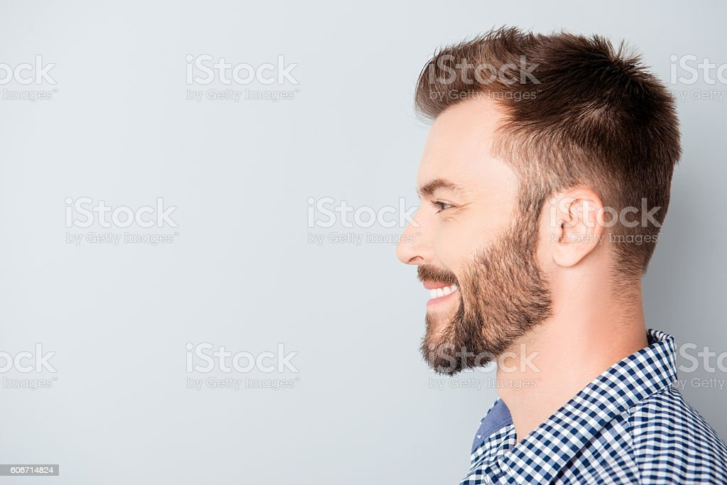 Side view of young happy smiling bearded man stock photo