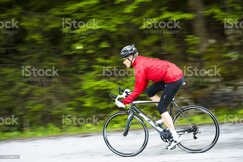 Side view of young male cyclist practicing stock photo