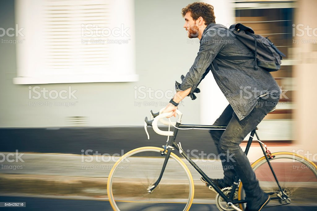 Side view of young man riding bicycle in city stock photo