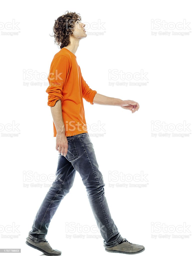 Side view of young man walking and looking upwards stock photo