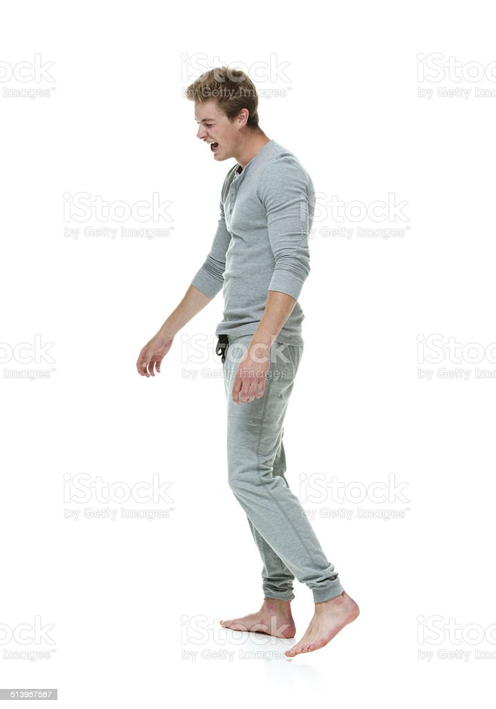 Side view of young man yawning and walking stock photo