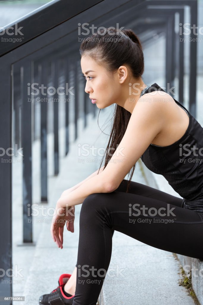 Side view of young sporty woman sitting on stadium stairs and looking away stock photo