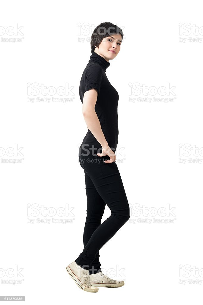 Side view of young woman in black turtleneck and pants stock photo