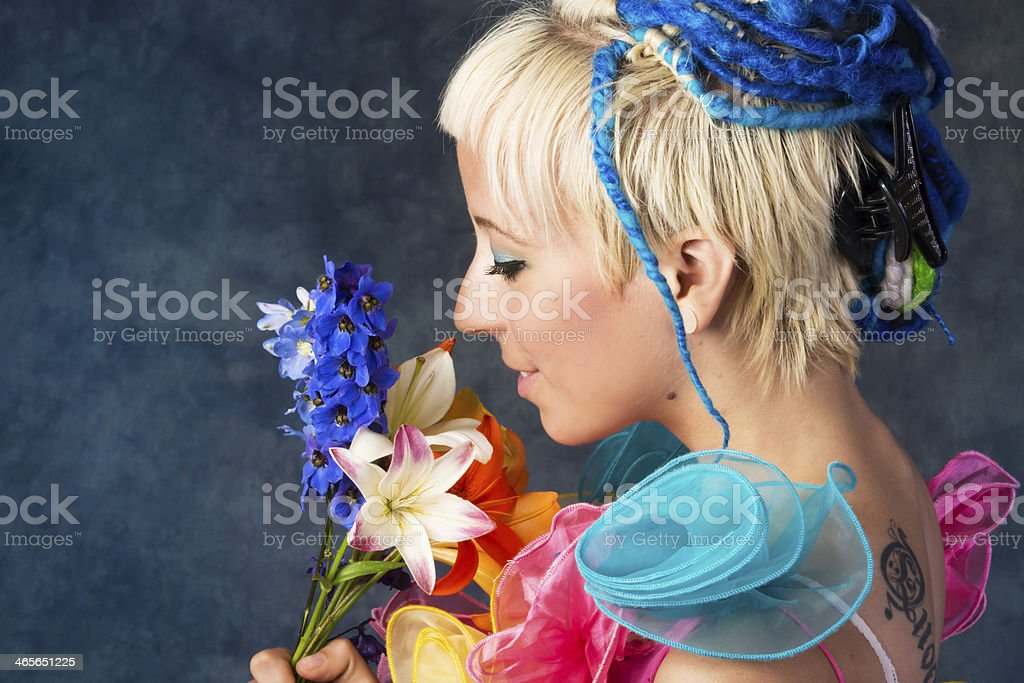 Side view of young woman looking at flowers. royalty-free stock photo