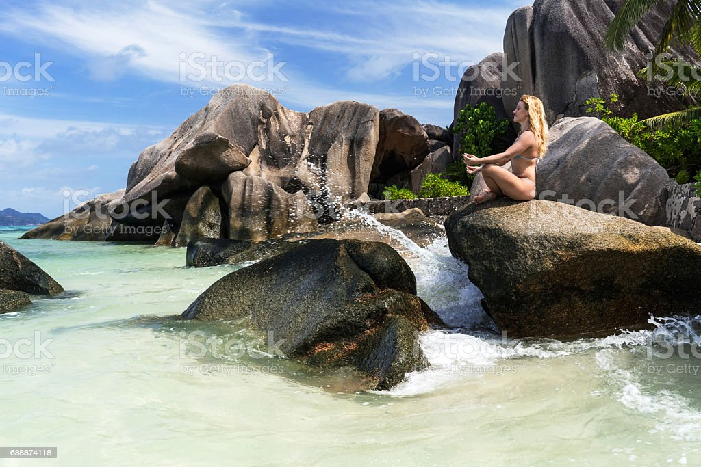 Side view of young woman meditating on a beach rock. stock photo