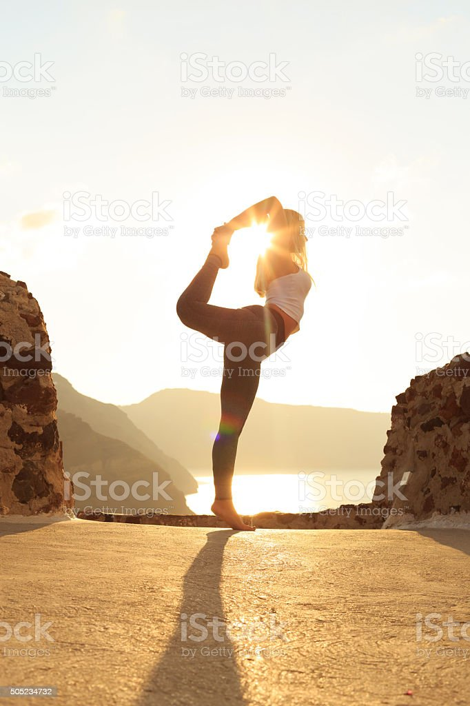 Side view of young woman standing on edge at rocks stock photo