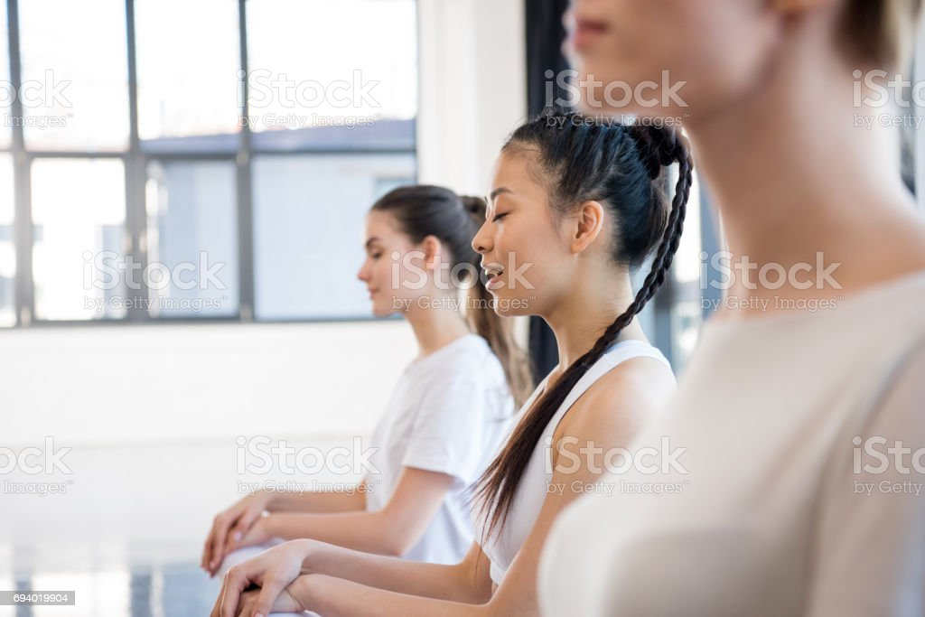 Side view of young women in sportswear meditating at yoga class stock photo