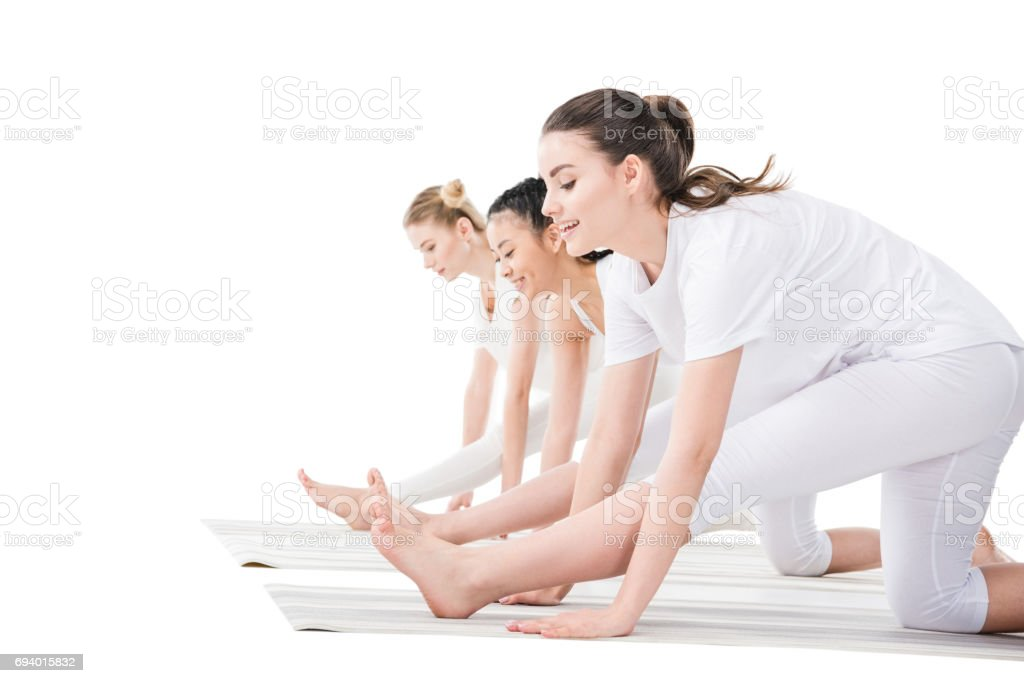 Side view of young women in sportswear practicing yoga isolated on white stock photo