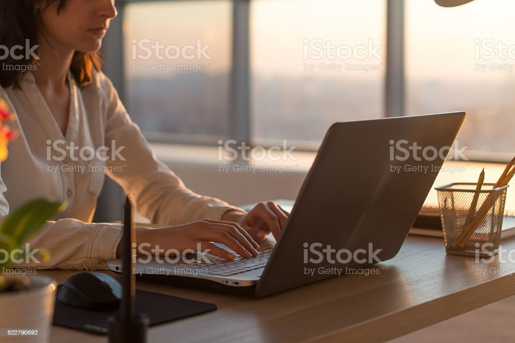 Side view photo of a female programmer using laptop, working stock photo