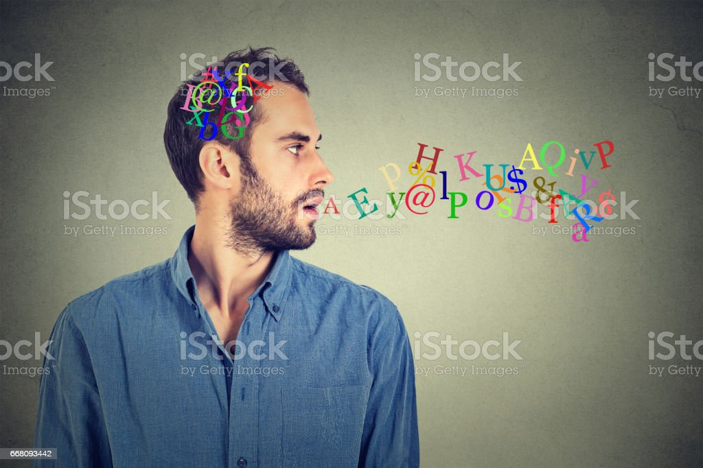 Side view portrait man talking with alphabet letters in his head and coming out of open mouth stock photo