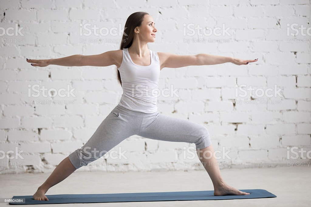 Side view portrait of happy woman doing Warrior II Pose stock photo