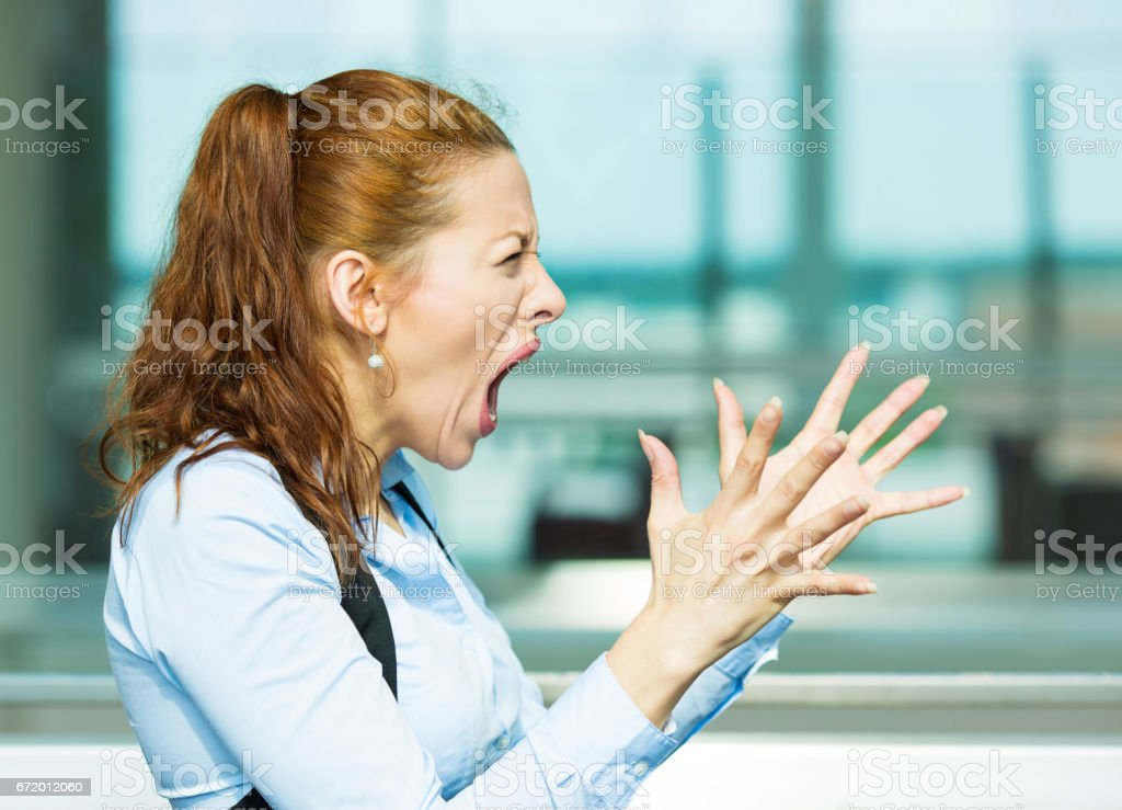 side view profile portrait mad angry, upset hostile young businesswoman, worker, furious yelling hands in air, stock photo