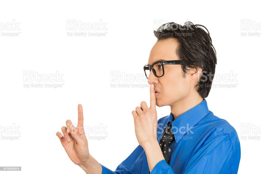 side view profile portrait young man placing finger on lips pointing to say shhh be quiet stock photo