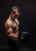 side view, profile young bodybuilder arm dumbbell exercise