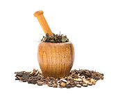 side view wooden mortar and pestle with herbs on white