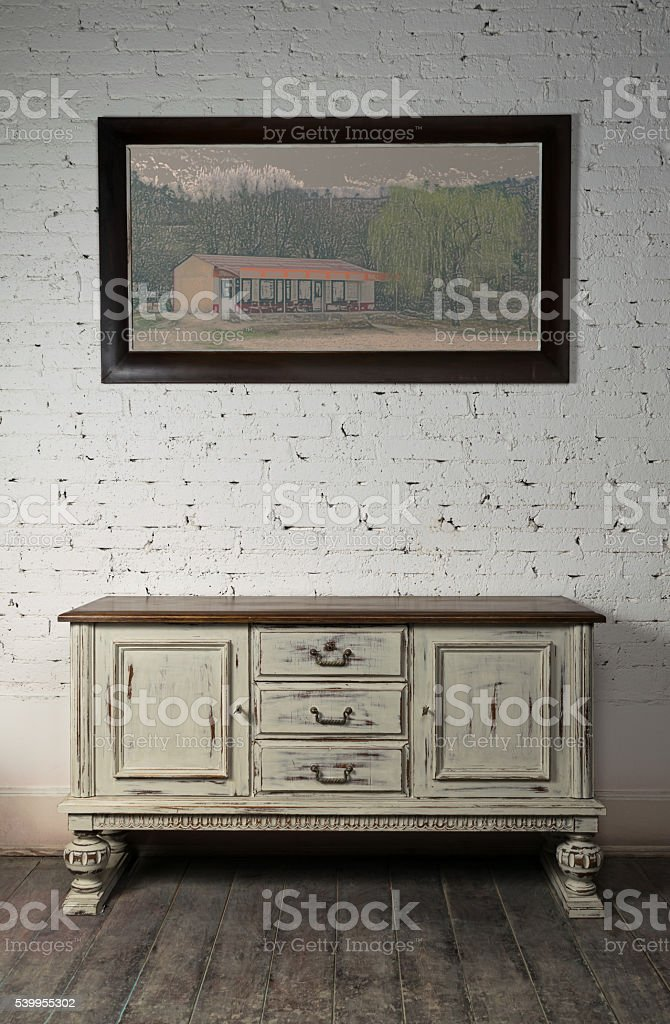Sideboard and  hanged painting over wooden floor and bricks wall stock photo
