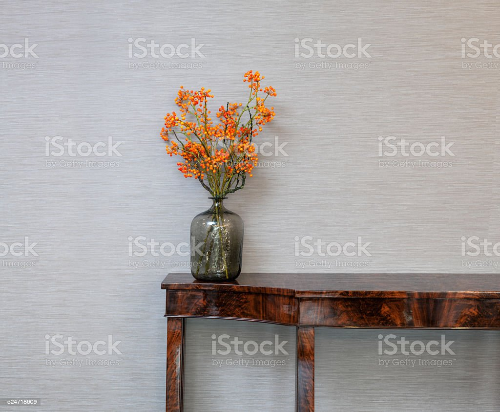 Sideboard in front of a grey wall with flower vase stock photo