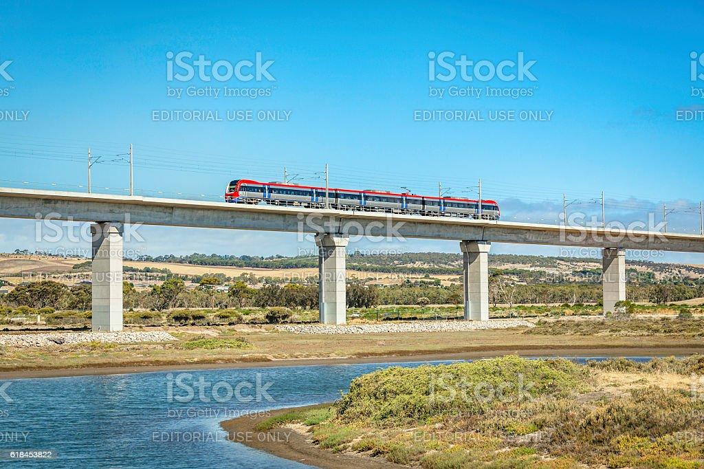 Side-view Adelaide Metro train crossing impressive Onkaparinga River rail-bridge stock photo