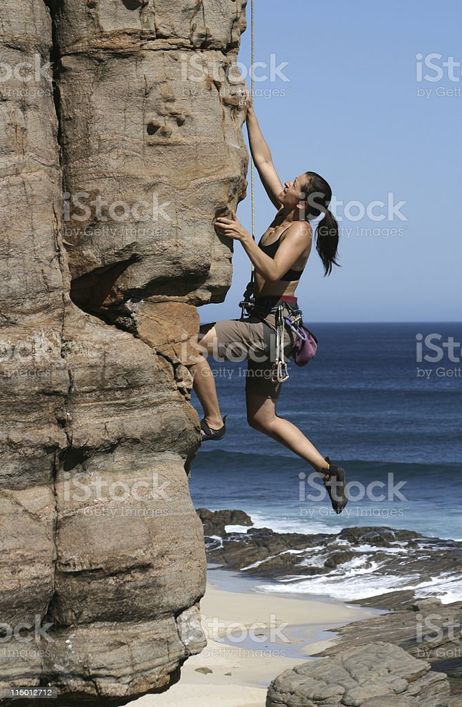 Side-view of a woman climbing a rocky cliff royalty-free stock photo