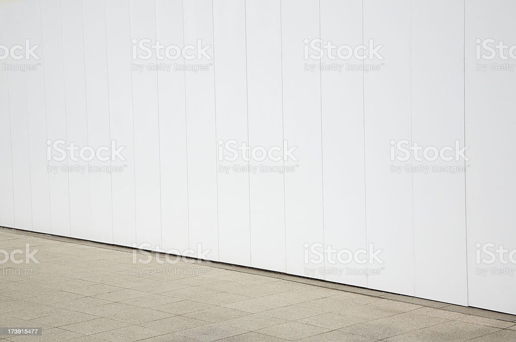 Sidewalk and white barrier wall royalty-free stock photo