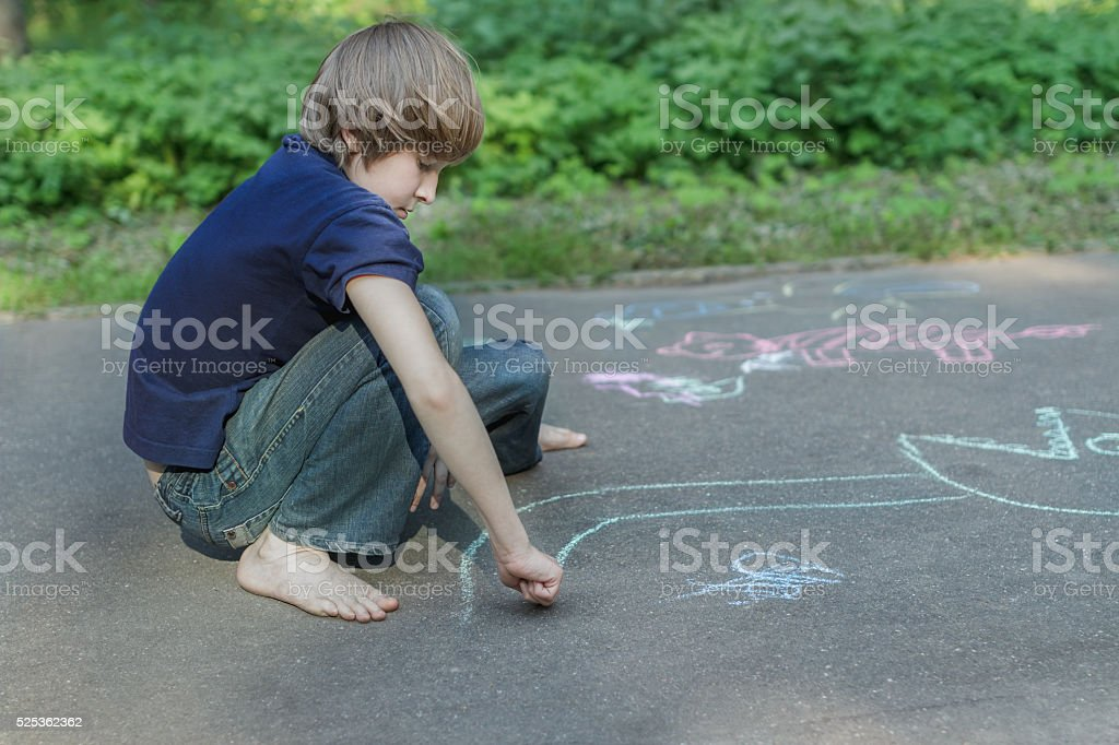 Sidewalk chalk drawings of barefoot teenage boy wearing blue t-shirt stock photo