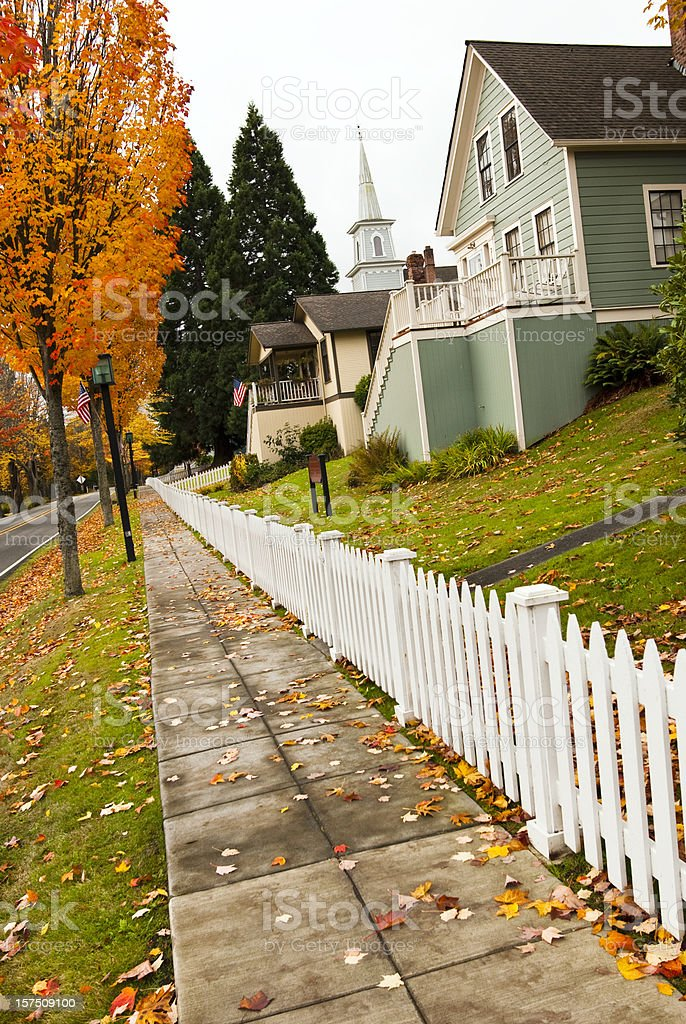 Sidewalk with white picket fence in small American town royalty-free stock photo