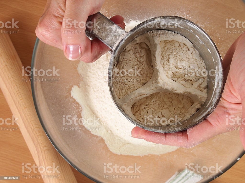 Sifting flour into bowl. Making Chocolate Layer Cake with Cream stock photo