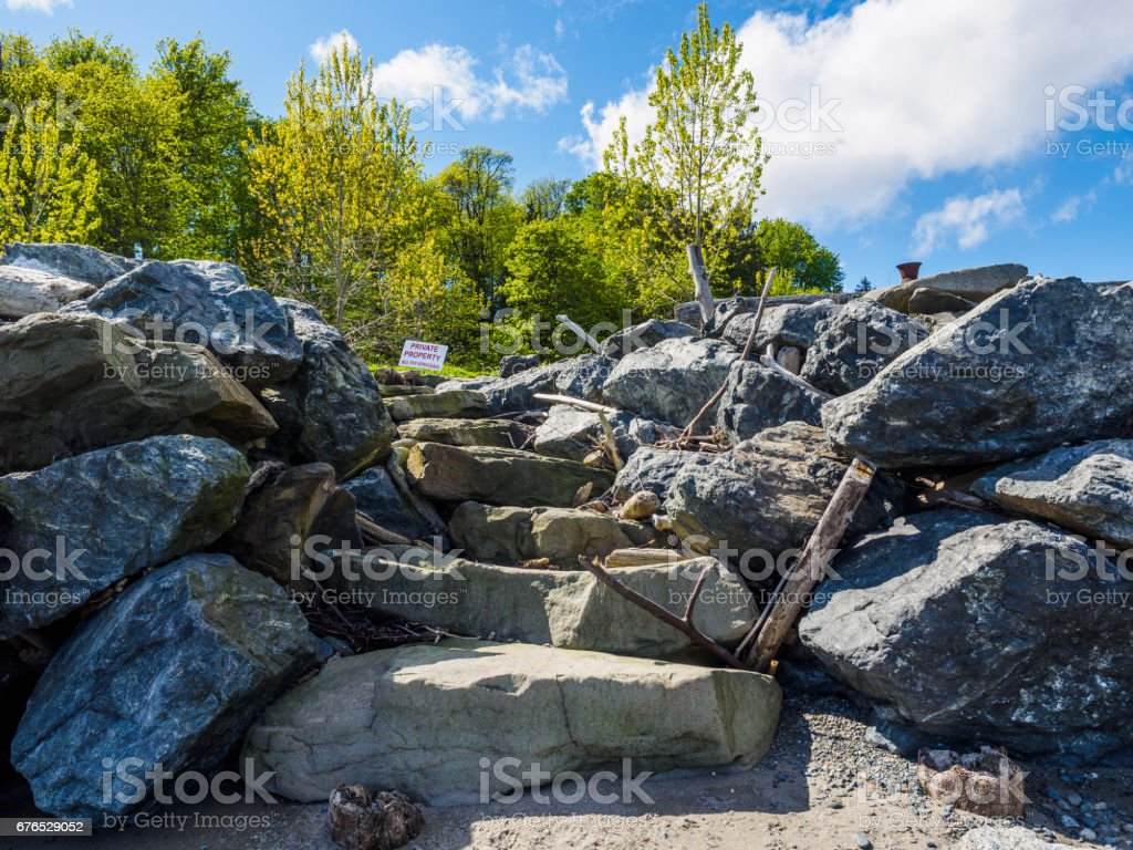 Sign alerting private property at the top of the steps in a retaining wall on the beach stock photo