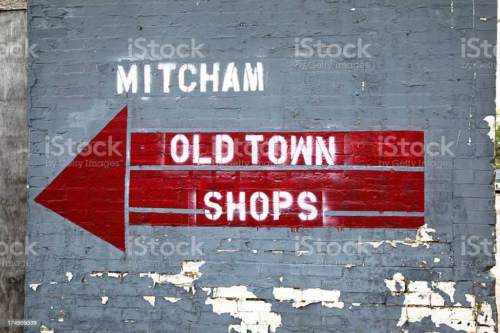 Sign and arrow on old building with peeling paint royalty-free stock photo