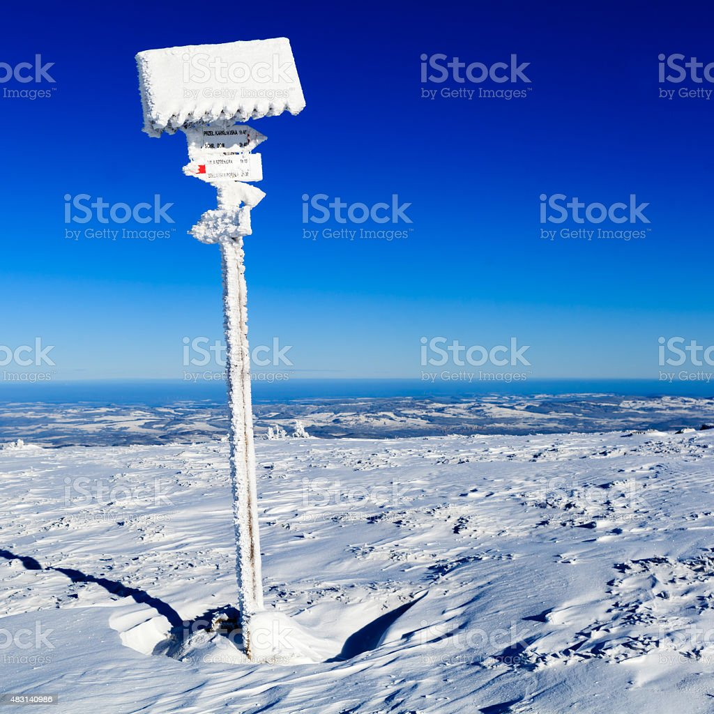 Sign and arrows in winter white mountains stock photo