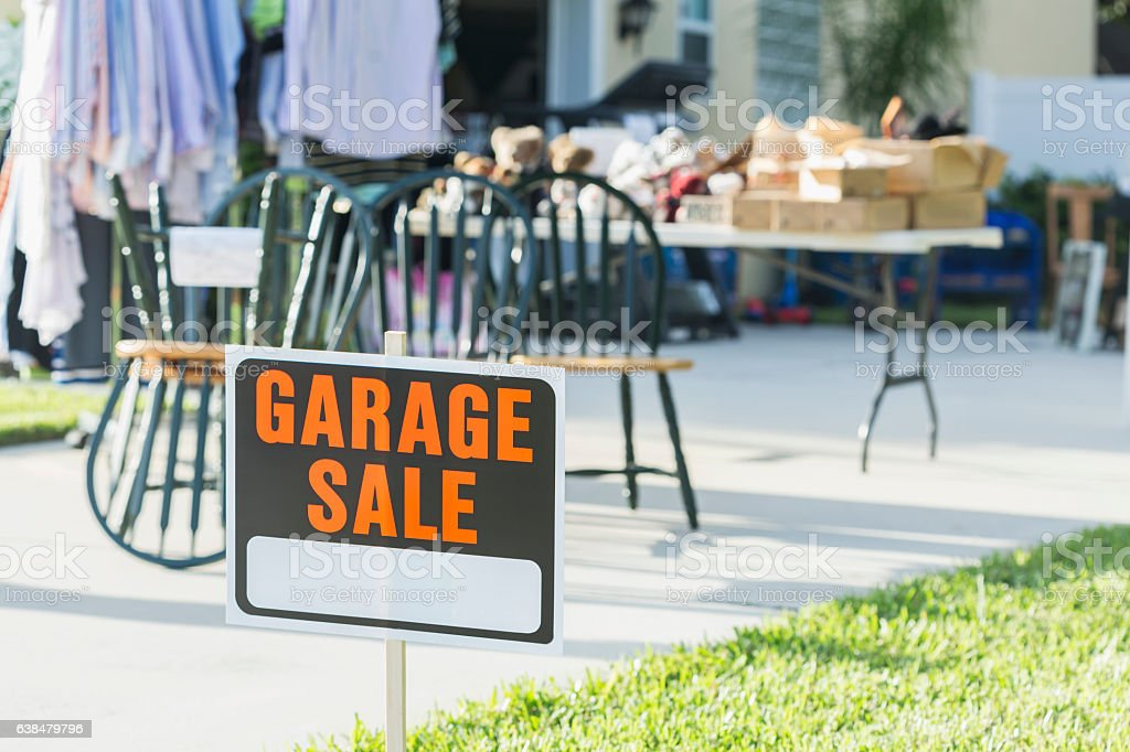 A sign at a garage sale. Out of focus in the background are a set of...
