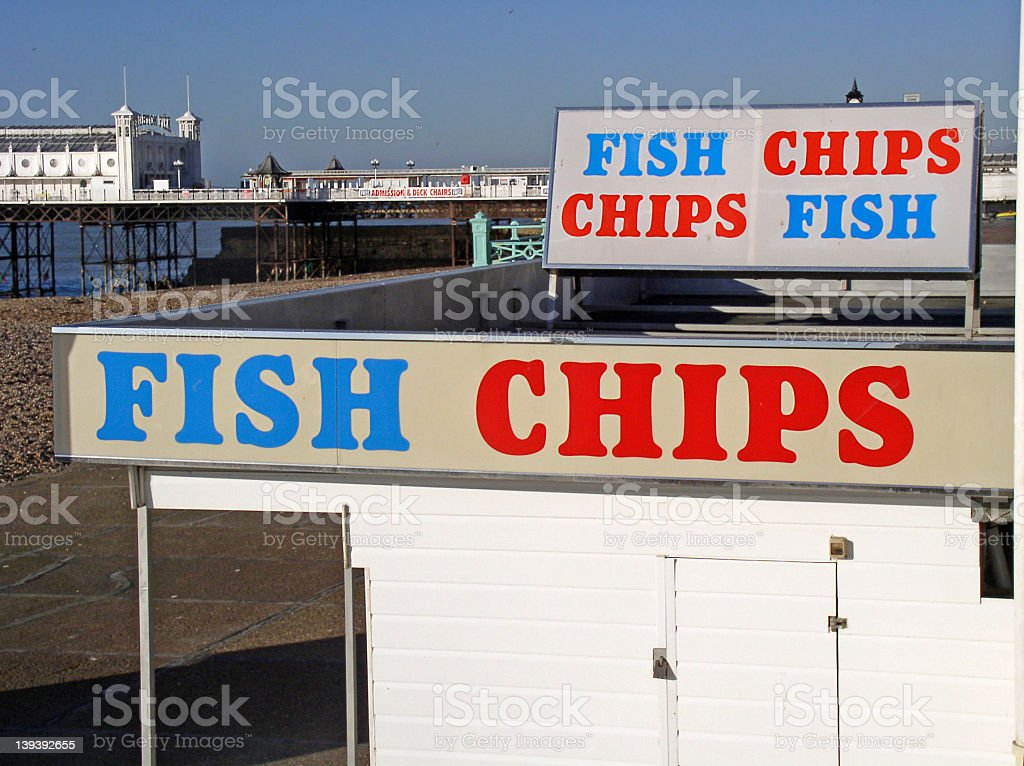 Sign for fish and chips on top of restaurant near ocean stock photo