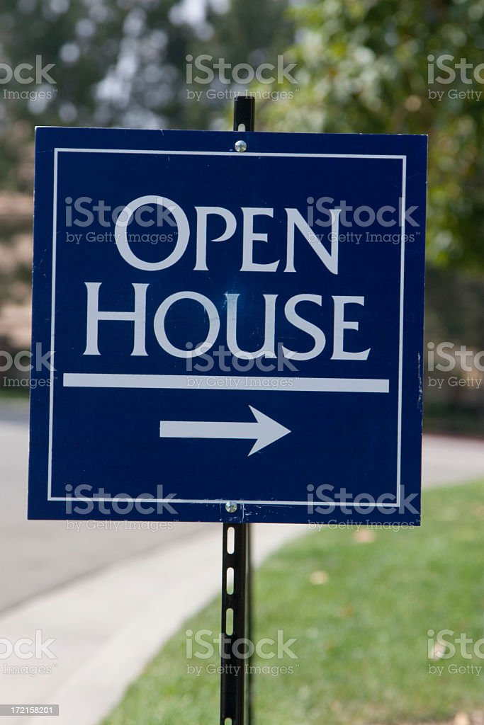 Sign for open house with right pointing arrow on green grass stock photo