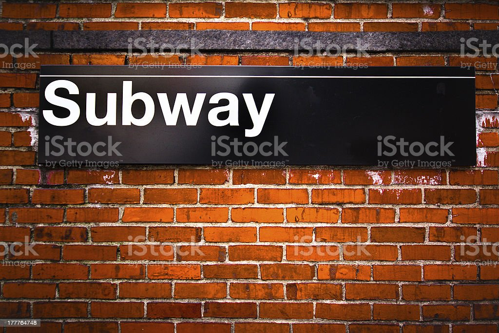Sign for the subway on a brick wall stock photo