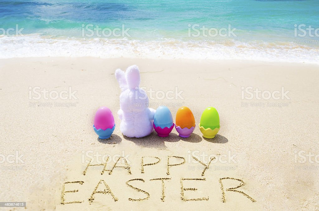 Sign Happy Easter with bunny and  eggs on the  beach stock photo