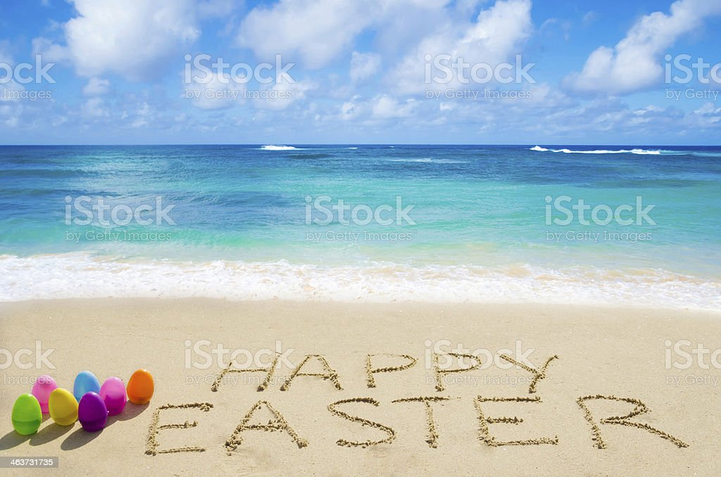 Sign Happy Easter with eggs on the beach stock photo
