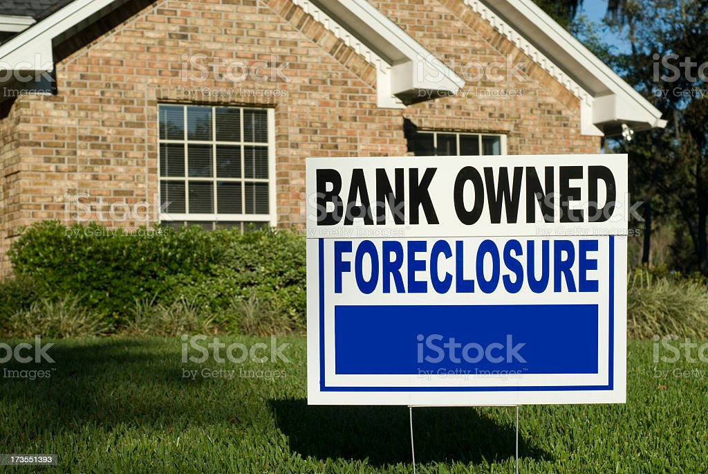 A sign in the yard of a house that says foreclosure stock photo