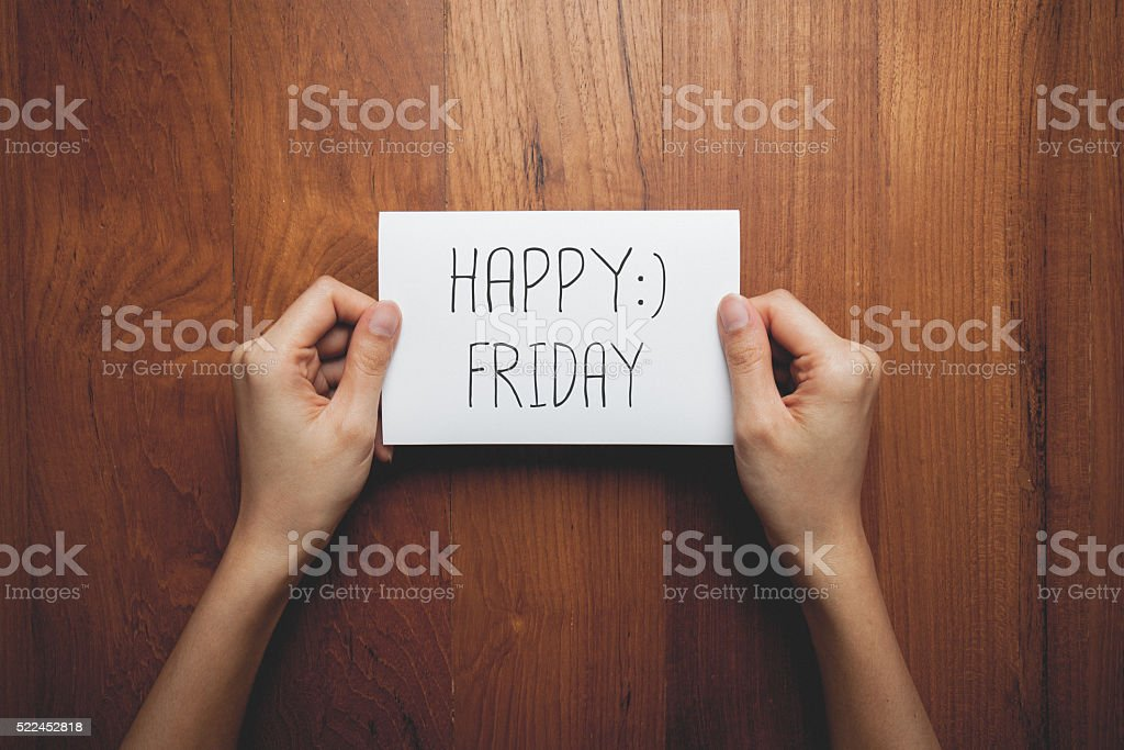 sign in woman's hands with the words happy friday stock photo