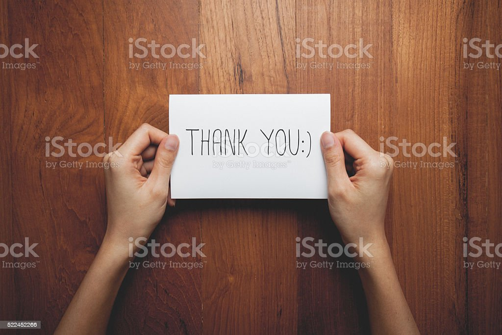 sign in woman's hands with the words thank you stock photo