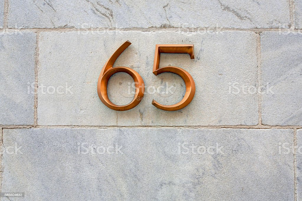 Sign of 65 on marble exterior wall stock photo