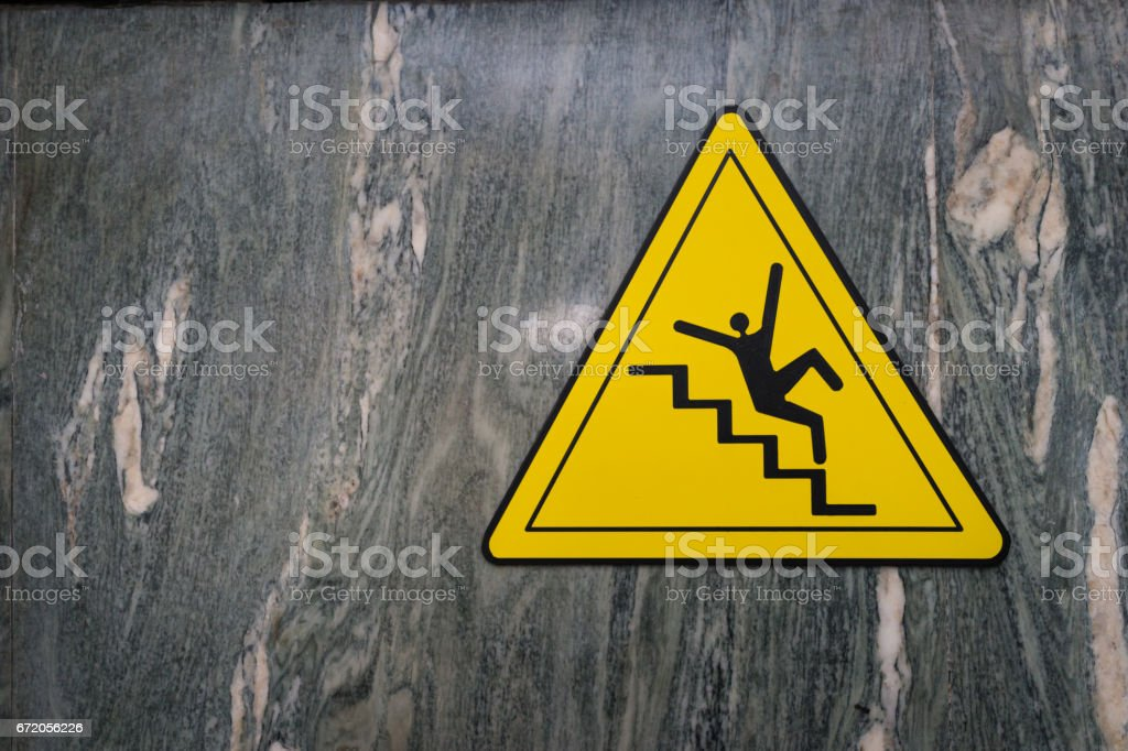 Sign of danger of falling stairs slip warning caution on marble wall stock photo