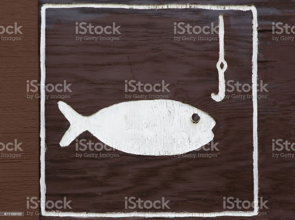 sign of white fish painted onto a brown painted board stock photo