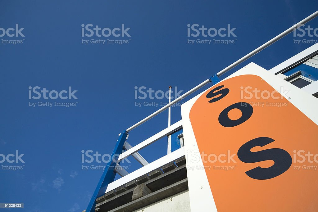 SOS sign on a lifeguard station along the coast royalty-free stock photo
