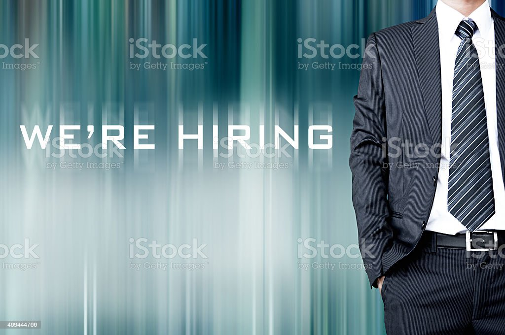 WE'RE HIRING sign on blur background with standing businessman stock photo