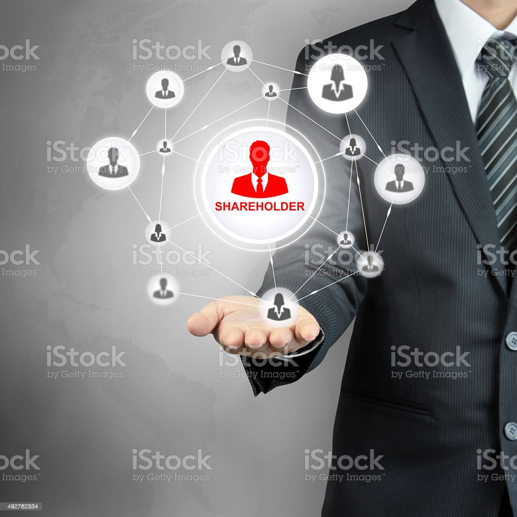 SHAREHOLDER sign on businessman hand stock photo