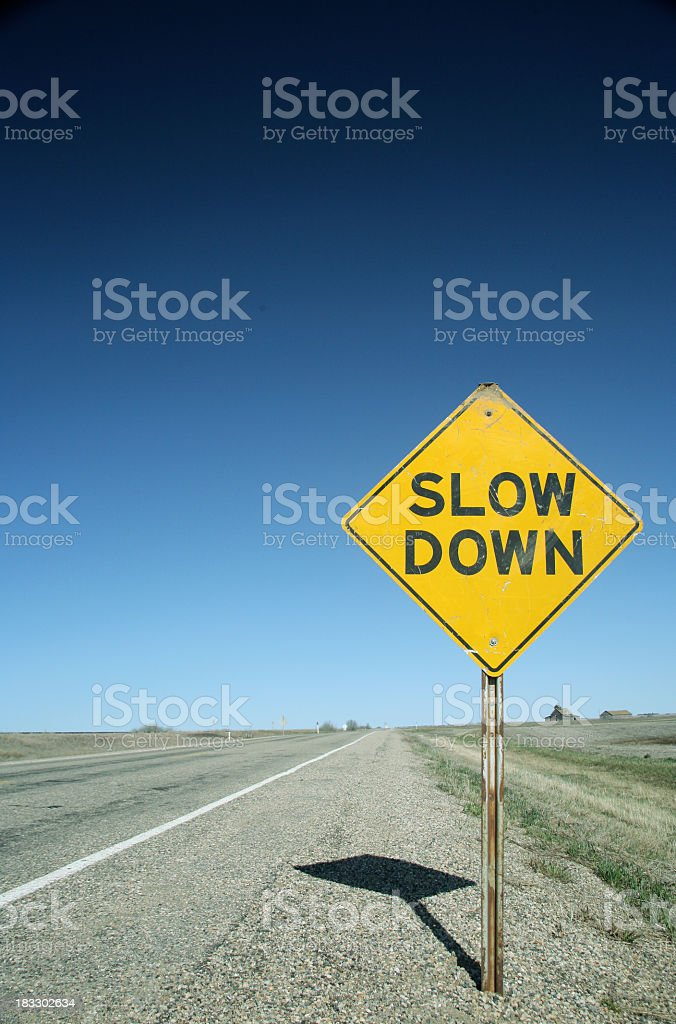sign on flat prairie road warns drivers to slow down royalty-free stock photo