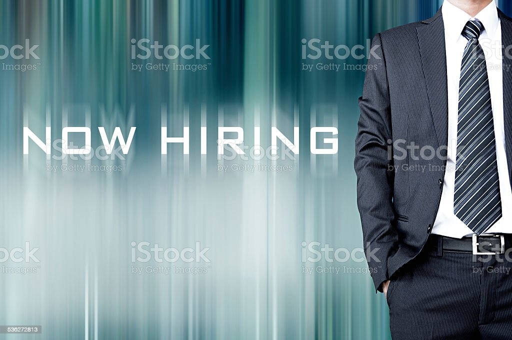 NOW HIRING sign on motion blur abstract background with businessman stock photo