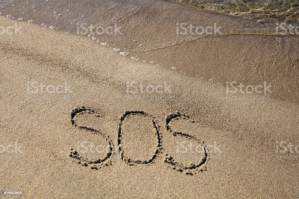 SOS sign on sandy beach stock photo