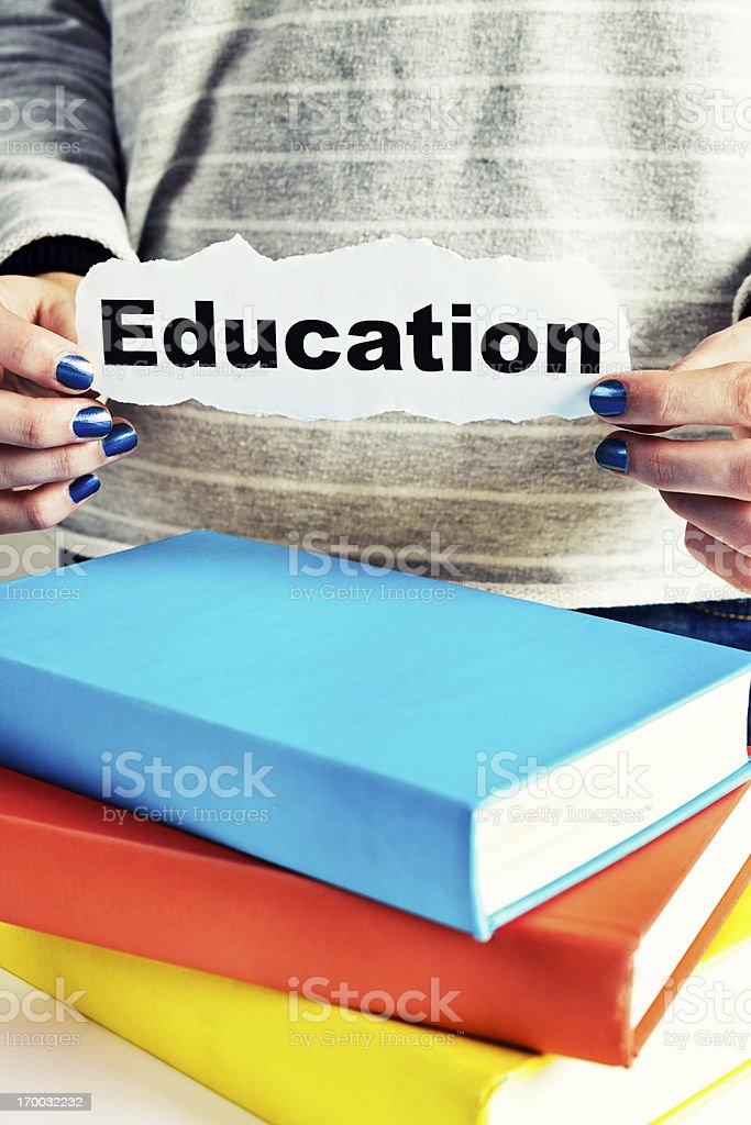 Sign reading Education held next to books: vital for success! royalty-free stock photo