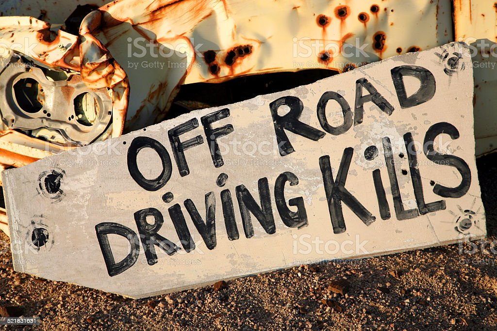 Sign saying off road driving kills on wreck stock photo